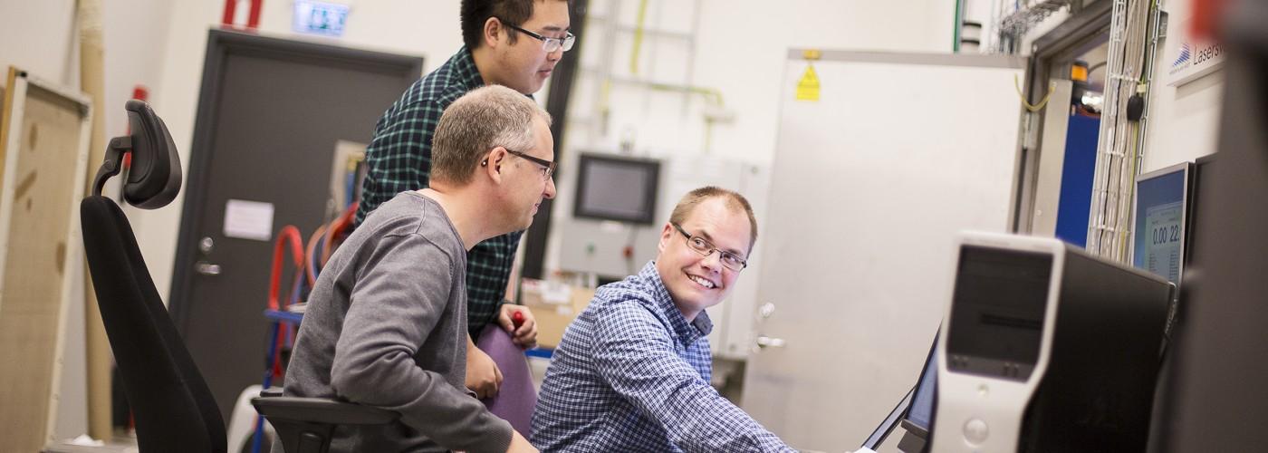 Tre män vid dator i industrimiljö