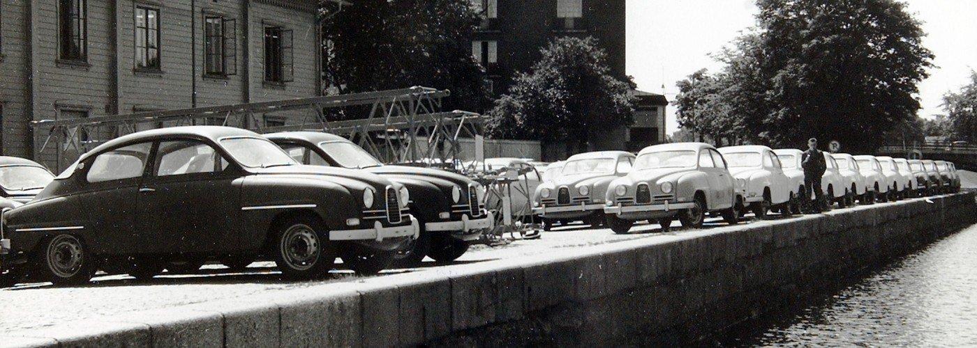 Saab 96 för export uppställda vid Strandgatan i Trollhättan år 1962. Arbetareföreningens hus och Stadshuset i bakgrunden.